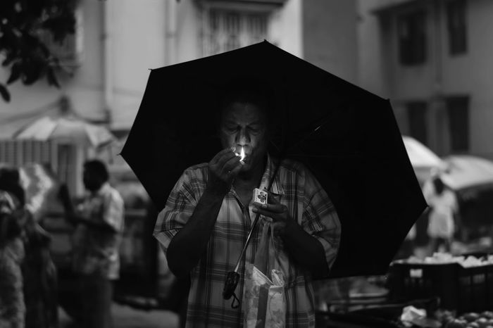 Blackandwhite Calcutta Focus On Foreground Front View Holding India Indiapictures Kolkatadiaries KolkataStreets Lights Men Portrait Raining Raining Outside Rainy Day Real People Smoking - Activity Street Streetphotography Umbrella