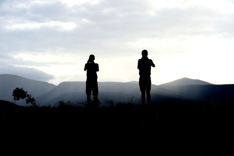 Silhouette Men Standing On Field By Mountains Against Sky