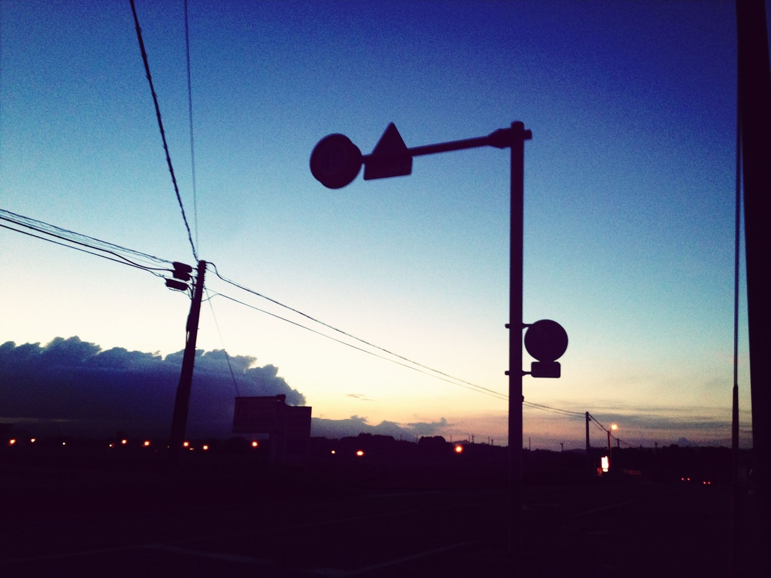 street light, sunset, silhouette, sky, communication, lighting equipment, road sign, power line, electricity, guidance, dusk, cable, road, electricity pylon, low angle view, pole, illuminated, street, building exterior, transportation