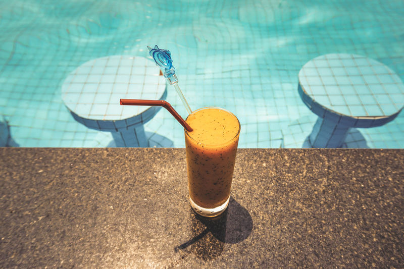 Close-up of drink on table at swimming pool