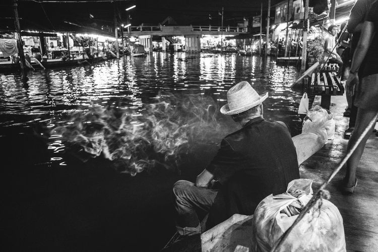 Man wearing hat sitting by canal in city at night