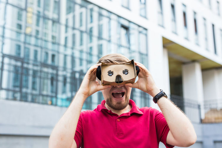 Man wearing virtual reality headset while standing against built structure