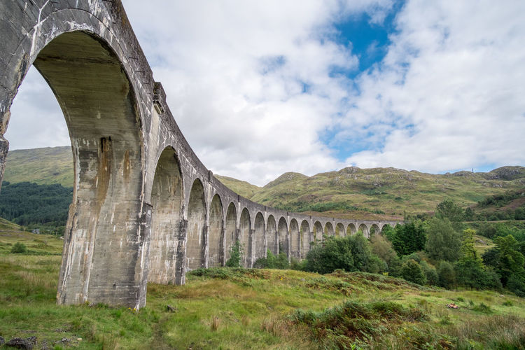 Glenfinnan Viaduct Harry Potter Architecture Built Structure Plant History Day Nature No People The Past Arch Viaduct Mountain Tree Bridge Green Color Bridge - Man Made Structure Arch Bridge Ancient Civilization Cloud - Sky Sky Grass Land Environment Landscape Outdoors Architectural Column