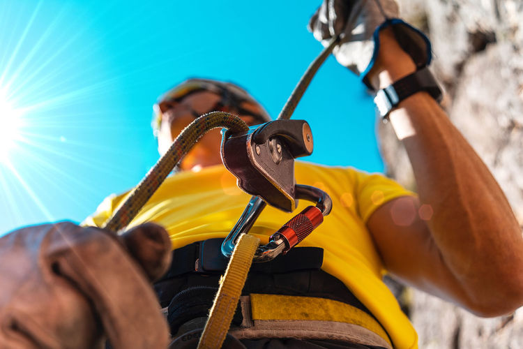 How to belay Day One Person Low Angle View Holding Selective Focus Men Outdoors Lifestyles Sunlight Sky Climb Climbing Yellow Alpinism Climbing A Mountain Mountain Bold Mountaineering Extreme Sports Sun Flare Rock Climbing Rock Climber Security