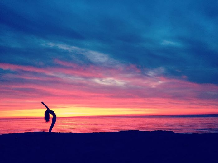Silhouette woman doing yoga by sea against cloudy sky during sunset
