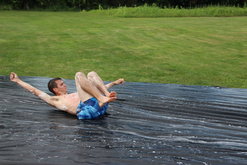 authentic red-neck slip and slide Fun Summer Fun ☀️ Day Family Fun Grass Leisure Activity One Person Outdoors Party Games People Redneck Redneck Good Times Redneck Summer Games Slip N Slide Water