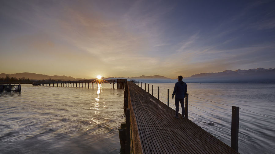 Moody Sky Rapperswil Beauty In Nature Full Length Holzsteg Lake Lake View Leisure Activity Lifestyles Men Mountain Nature One Person Outdoors Pier Real People Scenics - Nature Siluette Sky Standing Sunrise Sunset Tranquil Scene Tranquility Water