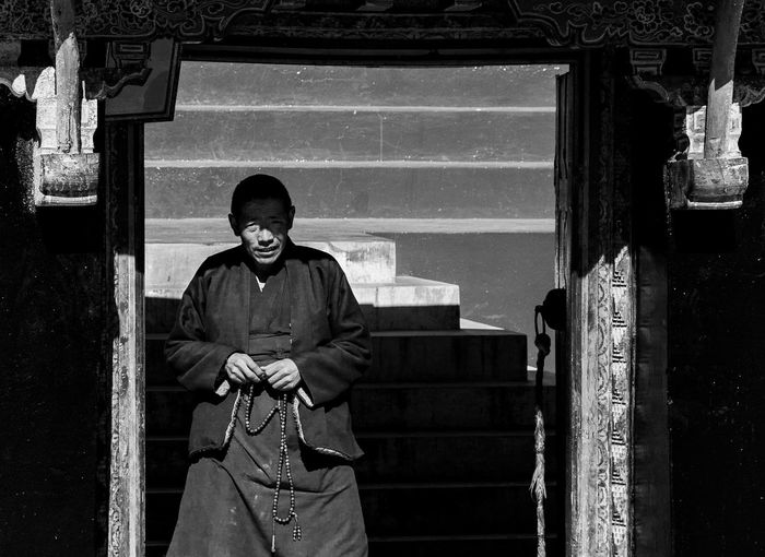 One Person Real People Front View Looking At Camera Portrait Three Quarter Length Standing Architecture Smiling Men Casual Clothing Built Structure Day Lifestyles Males  Leisure Activity Clothing Mature Adult Mature Men Monk  Tibetan  Tibetan Culture Tibetan Monk Blackandwhite Door Frame Staircase Shadows & Lights Tibet