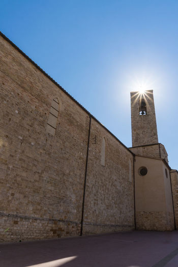 San Gimignano Tuscany Against The Sun Architecture Belief Building Building Exterior Built Structure Clear Sky Day History Italy Low Angle View Nature No People Outdoors Place Of Worship Religion Sky Spirituality Sunlight Sunstar Tower Wall Wall - Building Feature