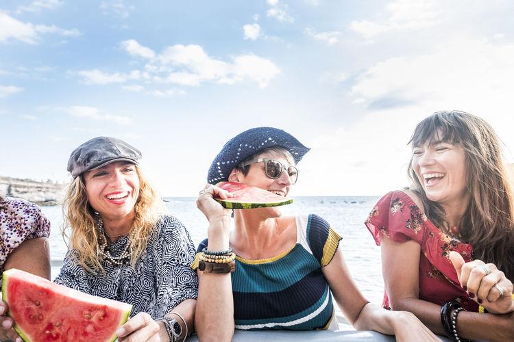 Smiling women eating watermelon against sky