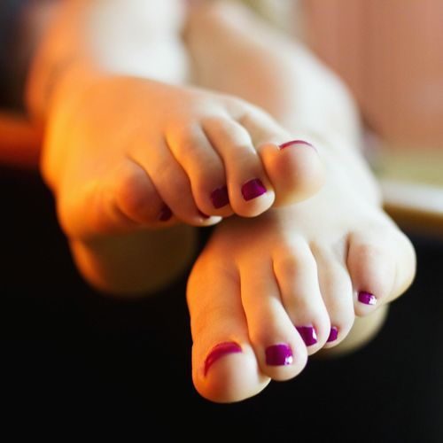 Low Section Of Woman With Purple Nail Polish At Home