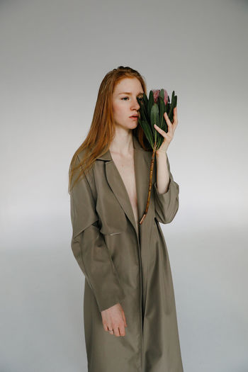 Studio Shot One Person Indoors  Young Adult Standing Gray Young Women Gray Background Beauty Women Beautiful Woman Hairstyle Front View Protea Protea Flower Flower Serious Ginger Gingerhair Redhair Style Fashion Fashion Model Fashion Photography Trench Coat Holding Sad Thoughtful Hair Long Hair Adult Three Quarter Length
