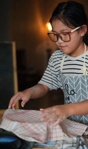 Full length of a boy holding eyeglasses