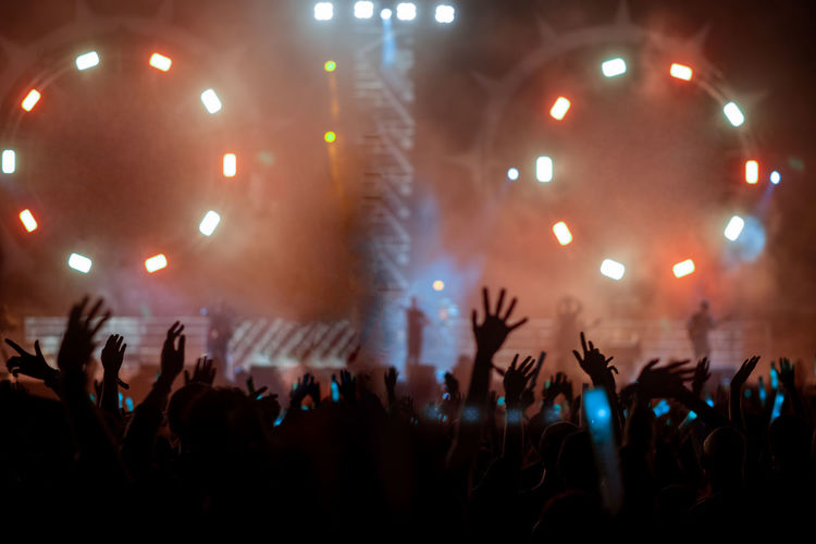 Crowd with arms raised enjoying at music concert