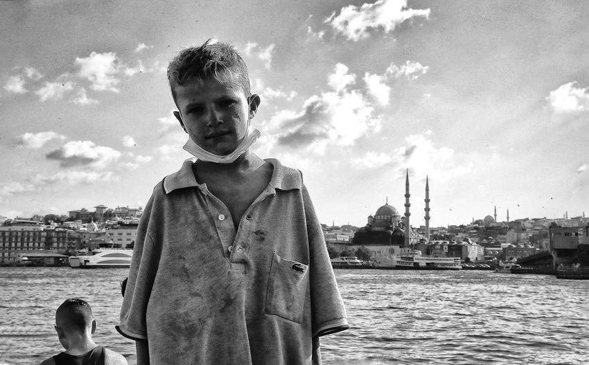 Portrait of boy in water against sky