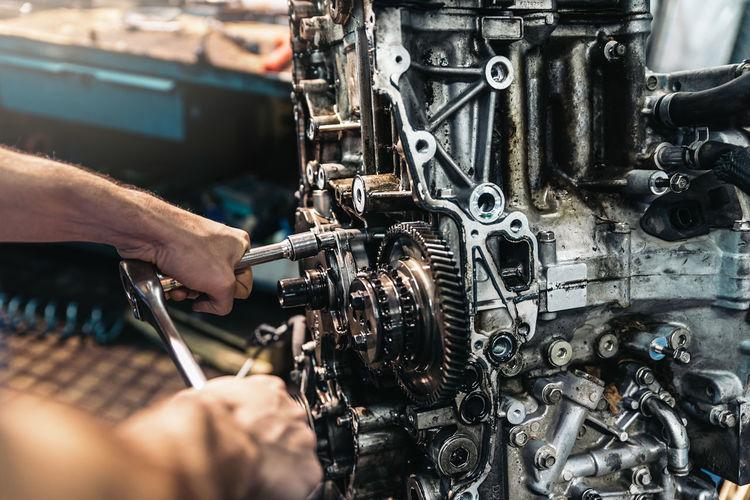 Close-up of man repairing machinery