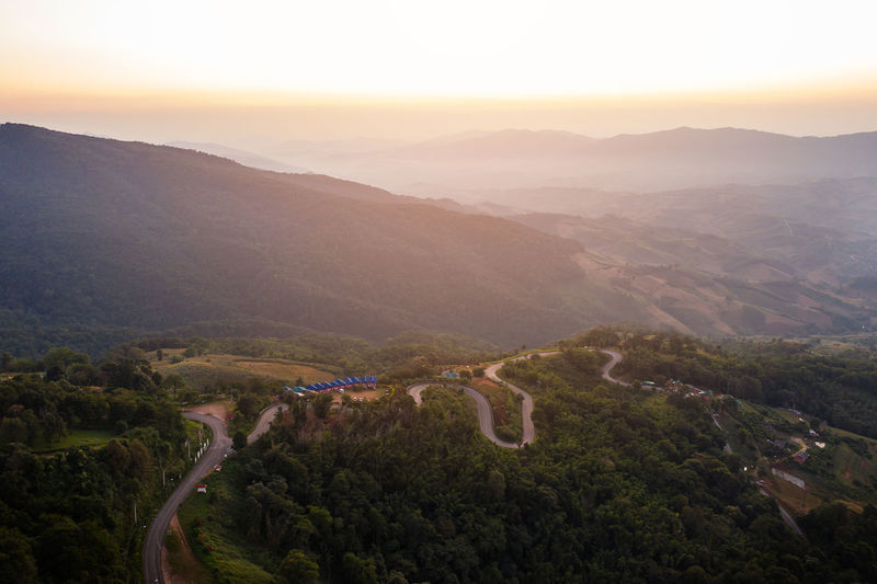 High angle view of winding road against sky during sunset