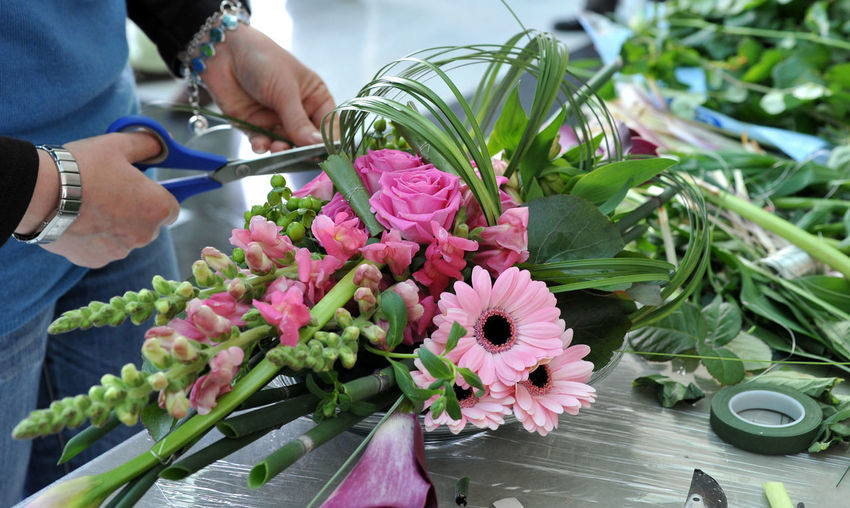 Close-up of florist making bouquet at table