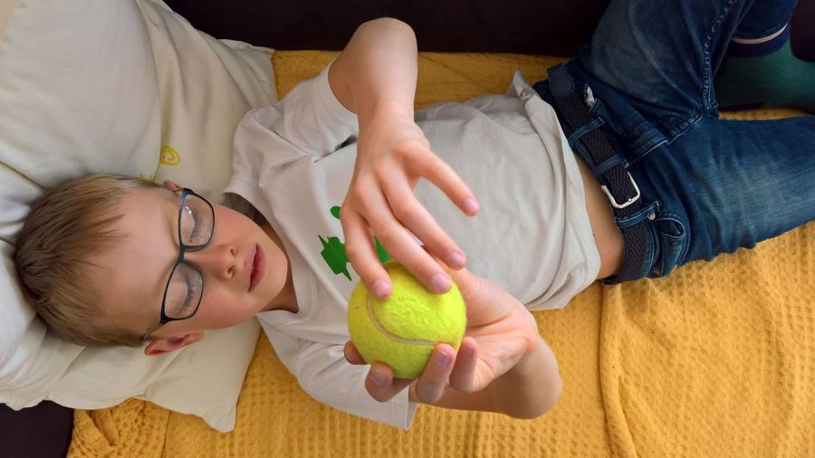 16x9 Happiness Males  Tennis Ball Boy Casual Clothing Child Childhood Emotion Holding Indoors  Leisure Activity Lifestyles Lying Down People People Photography Positive Emotion Relaxation Smiling Togetherness Wellbeing