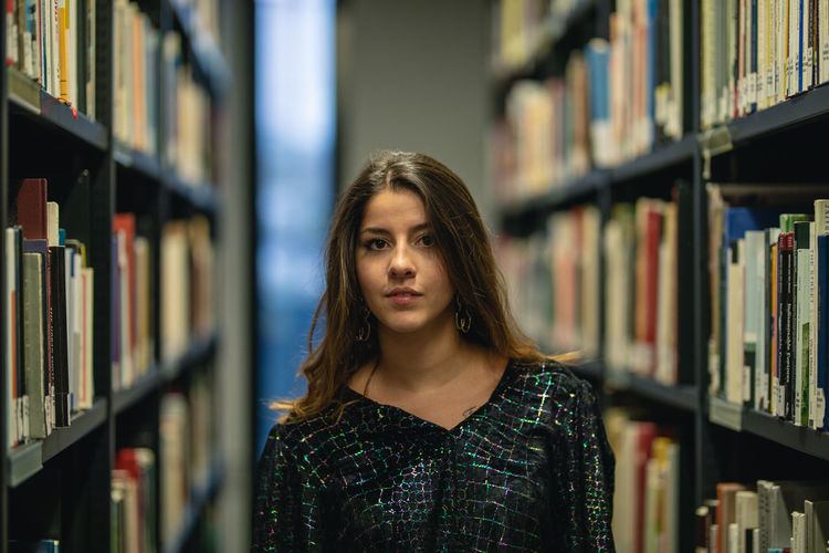 Portrait of young woman standing amidst bookshelf at library