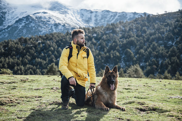 Full length of man with dog standing on mountain