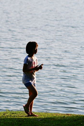 Side View Of Girl Holding Mobile Phone While Standing By Lake