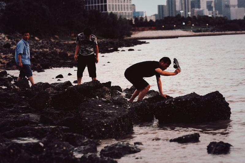 Children on rock at sea shore