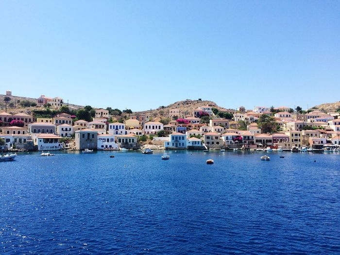 Townscape in front of sea against clear sky at halki