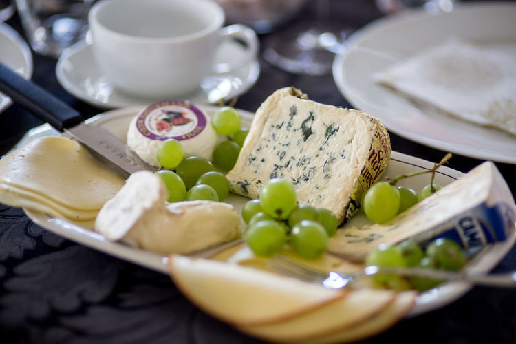 Close-Up Of Cheese With Grapes Served On Table