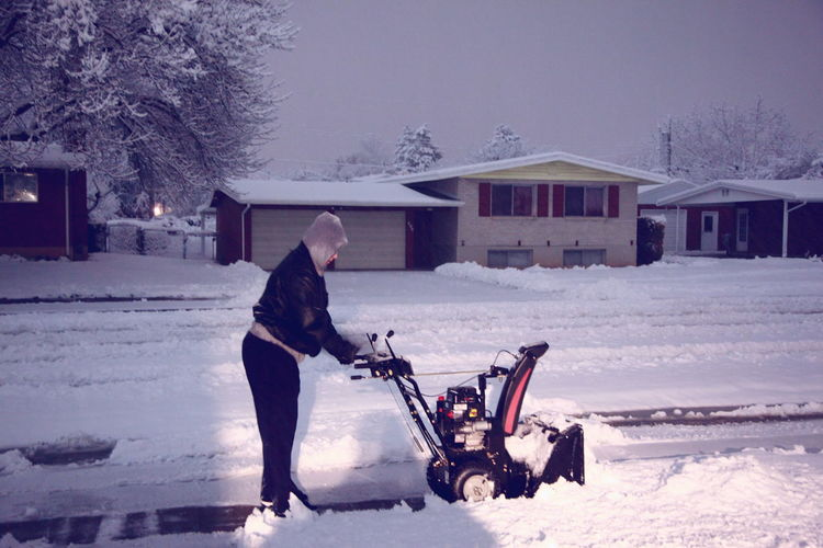 Side view of woman plowing snow with machinery