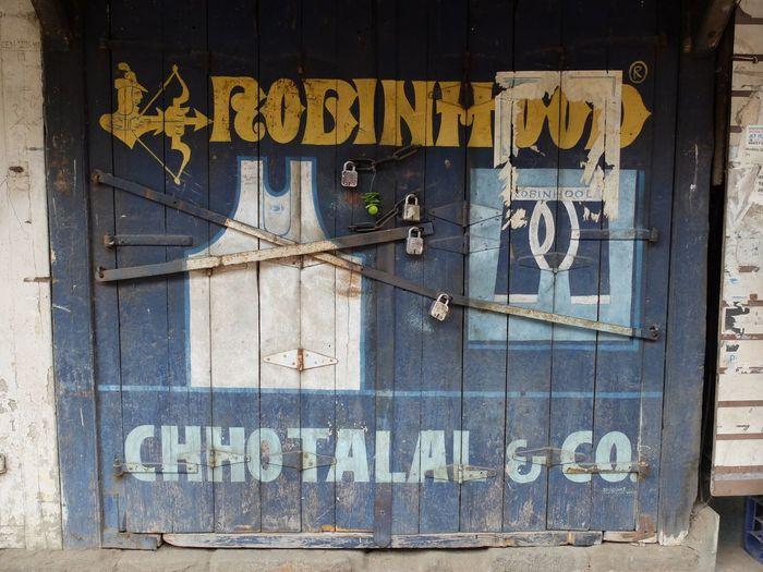 Blue Built Structure Corner Store Directional Sign Indoors  Information Sign No People Poster Robinhood Shop Text Third World Thirdworld Western Script First Eyeem Photo