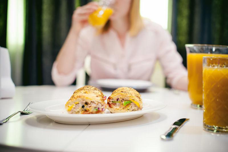 Food against woman drinking orange juice on table