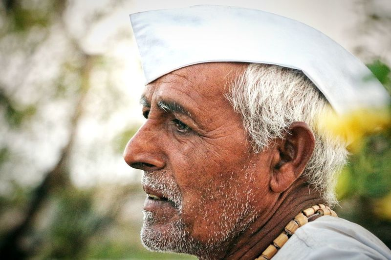Side view of thoughtful senior man wearing white cap