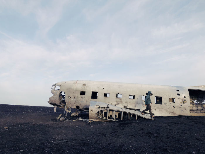 Side View Of Man Walking By Abandoned Airplane Against Sky