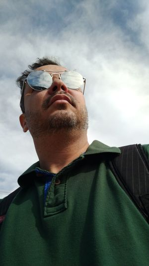 Low angle view of man wearing sunglasses against sky
