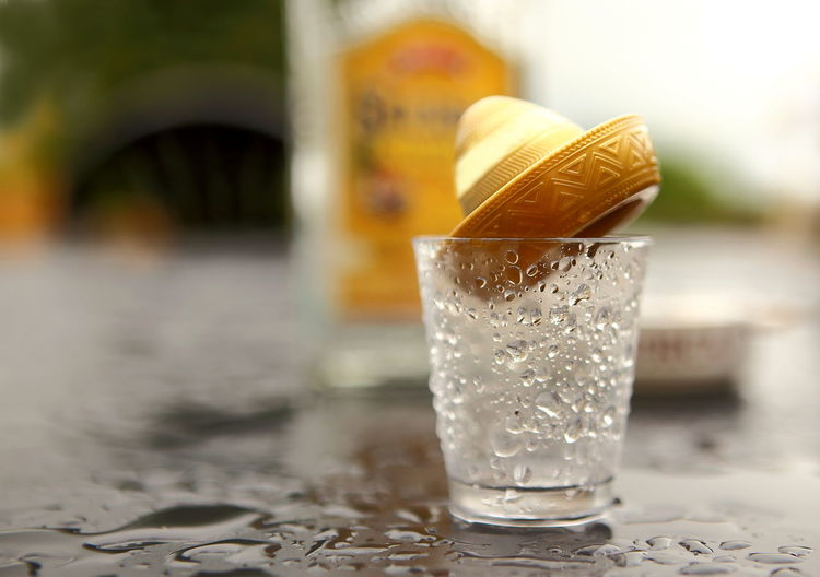 Close-up of wet tequila glass on table