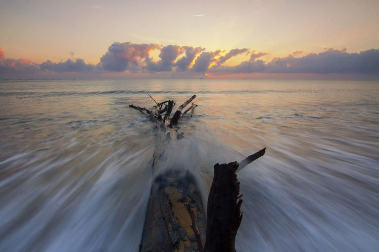 Water Sky Sea Sunset Scenics - Nature Beauty In Nature Nature Motion Tranquility Tranquil Scene Splashing No People Non-urban Scene Land Long Exposure Horizon Over Water Beach Cloud - Sky Orange Color Outdoors Driftwood