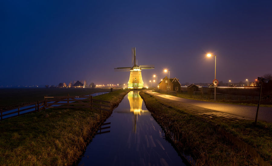 Alternative Energy Architecture Built Structure Canal Dusk Environmental Conservation Fuel And Power Generation Illuminated Light Lighting Equipment Nature Night No People Outdoors Renewable Energy Sky Street Street Light Turbine Water Wind Power Wind Turbine