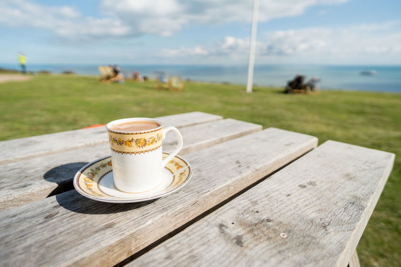 Walimex 12mm Cappuccino Close-up Coffee - Drink Coffee Cup Day Drink Focus On Foreground Food And Drink Freshness Froth Art Frothy Drink Grass Horizon Over Water Nature No People Outdoors Refreshment Sea Sky Table Water Wood - Material