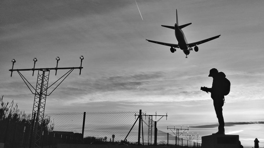 Silhouette man standing against sky with airplane