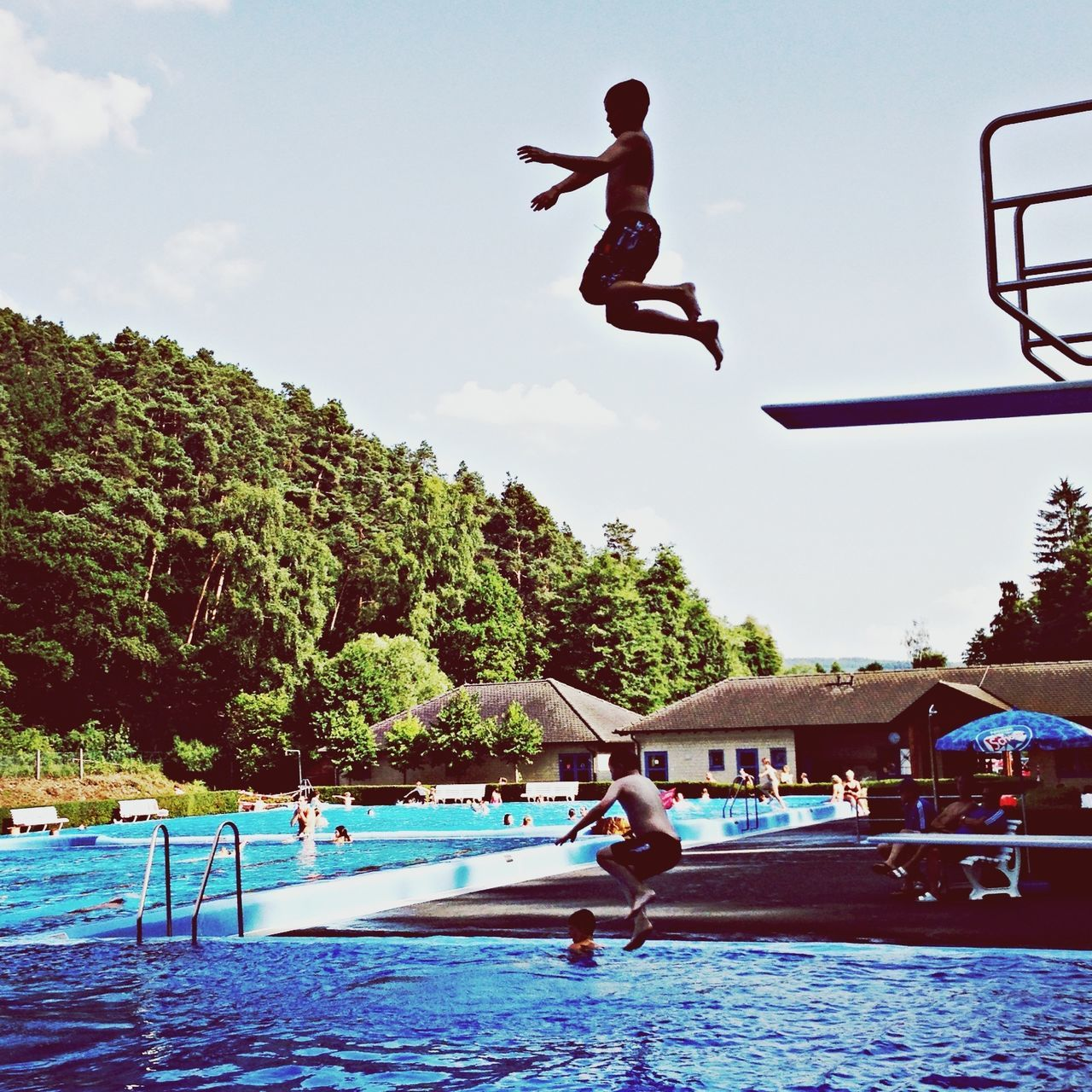 Man jumping into swimming pool against sky