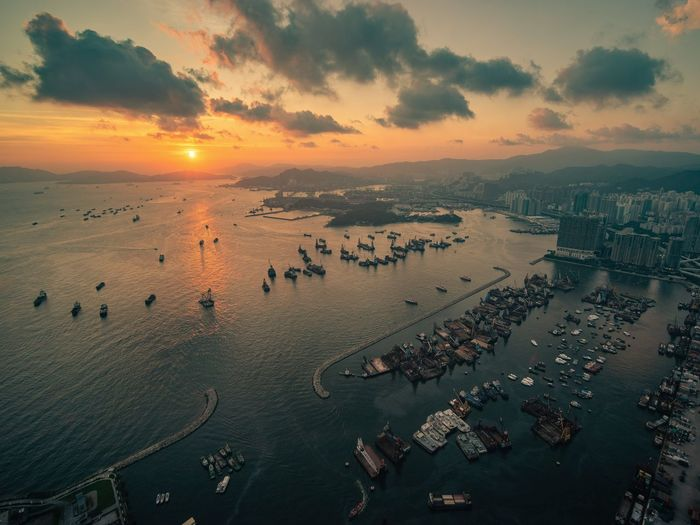 High angle view of hong kong city and bay against sky during sunset