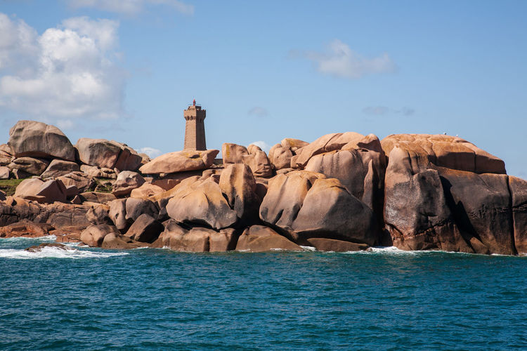 Lighthouse amongst pink granite boulders, ploumanach coast, brittany, france
