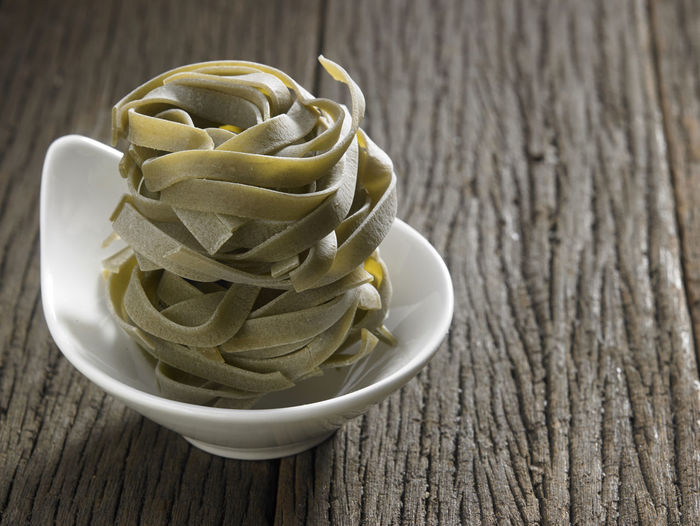 bowl of tagliatelle on the wooden background Food And Drink Spaghetti Tagliatelle Wheat Wood Grain Carbohydrate - Food Type Close-up Fettuccine Food Healthy Eating High Angle View Ingredient Italian Food No People Pasta Raw Food Still Life Table Wood - Material Yellow