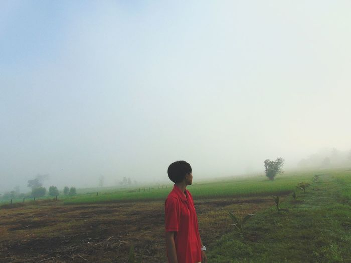 Rear view of boy standing on field against clear sky