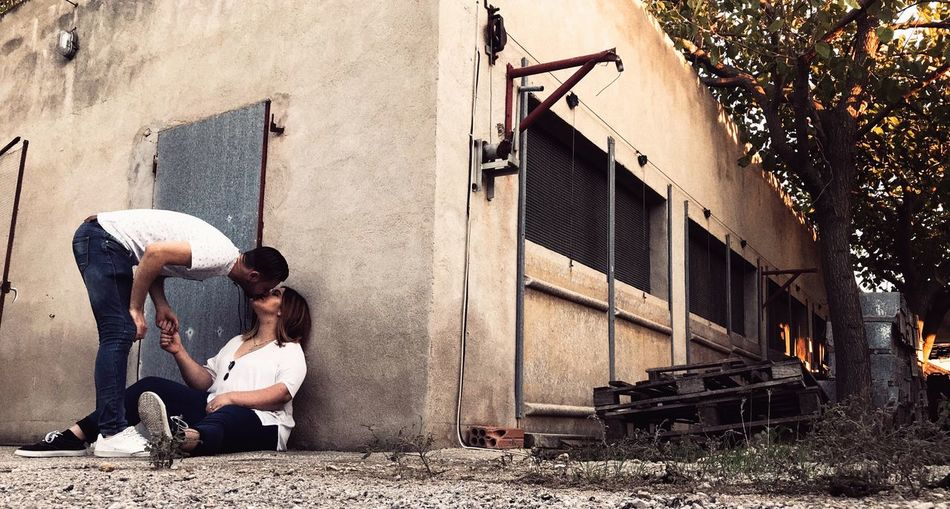 Couple Kissing On Footpath Against Building