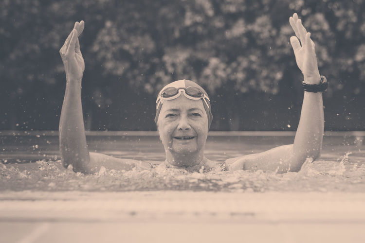 Portrait of smiling woman swimming in pool