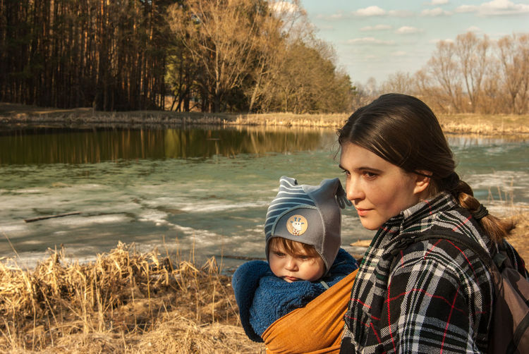The spring sun is melting the winter ice away Baby Baby Sling Baby Wrap Babywearing Bonding Childhood Children Countryside Day Family Frozen Lake Ice Lake Lakeshore Lifestyle Love Maternity Mom Mother And Son Motherhood Outdoors Parenting Pond Sling Woman