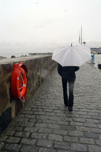 Rear view of people walking on footpath during rainy season
