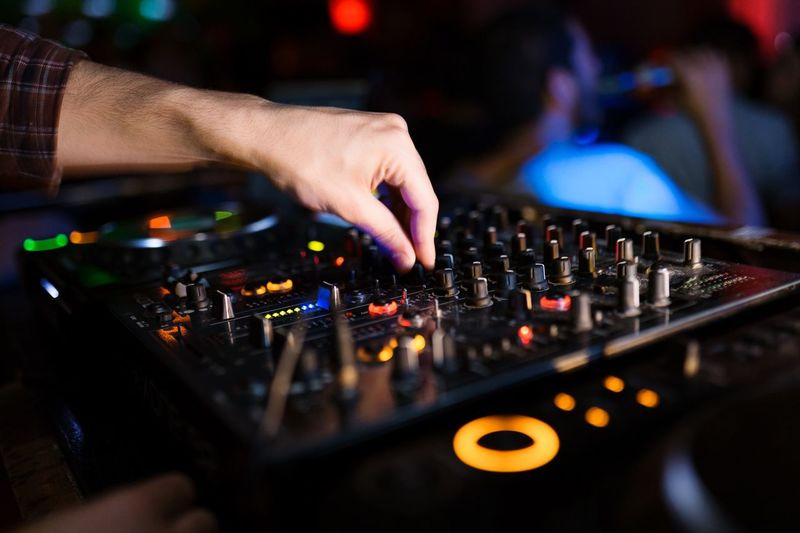 Cropped Hand Of Dj Using Sound Mixer At Night